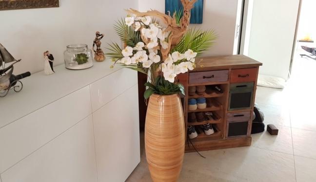 Künstliche Blumen arrangiert zu einem Kunstblumen Arrangemenst, das in einem Wohnzimmer steht.