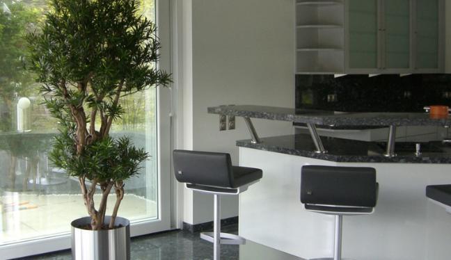 Massgefertigter Premium Kunstbaum in einem edelstahl Topf, der in einer Küche steht.