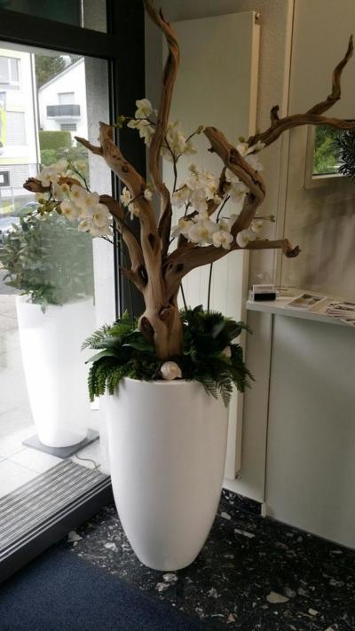 Grosses Kunstblumen Gesteck mit Holz dekoriert in einem weissen Pflanzgefäss.