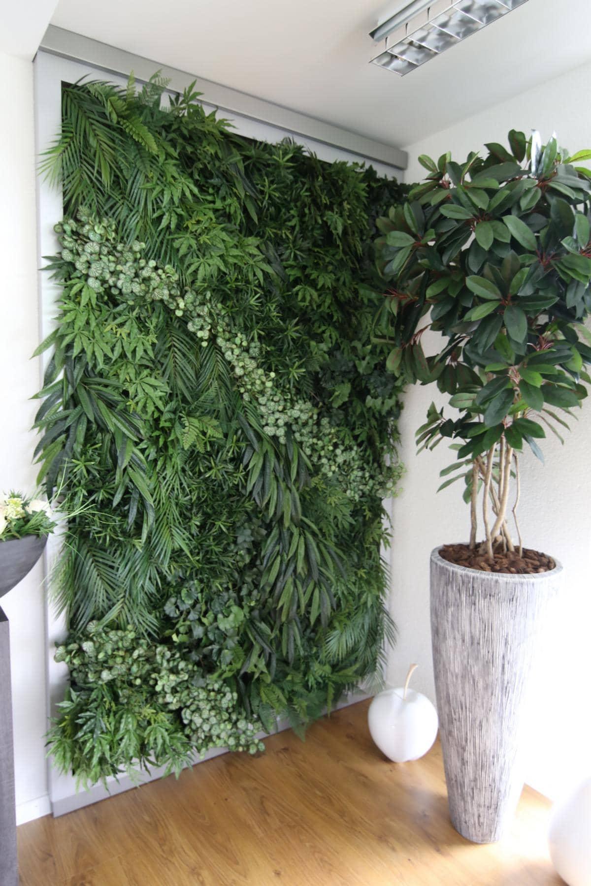 Künstliche Pflanzenwand und Topf mit Pflanze in einem Büro.