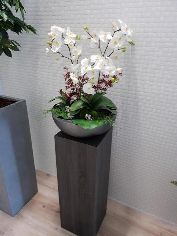 Gesteck aus Kunstblumen in Schale auf einer Pflanzsäule.