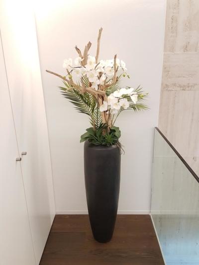 Raumbegrünung mit Kunstblumen dekoriert mit Holz in einem hohen Gefäss.