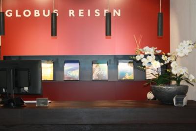 Raumbegrünung mit einem Kunstblumen Gesteck in einem Reisebüro.
