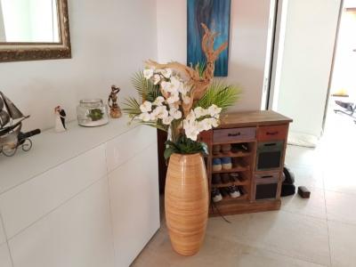 Kunstblumen Gesteck dekoriert mit Holz in einer Vase.