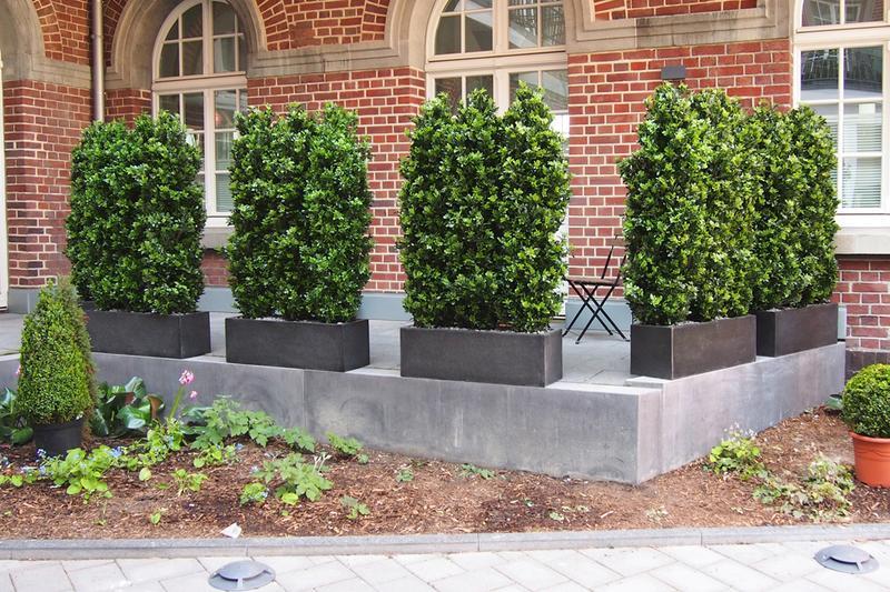 Sitzplatzgestaltung mit Lorbeer Kunsthecken auf eine Terrasse.