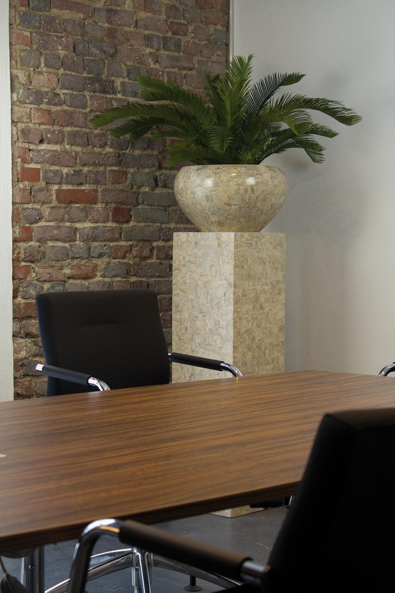 Hochwertige Kunstpflanze in Schale auf Sockel in einem Sitzungszimmer.