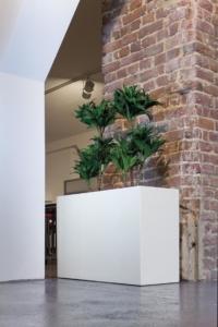 PFlanzgefäss mit Kunstpflanze als Raumteiler.