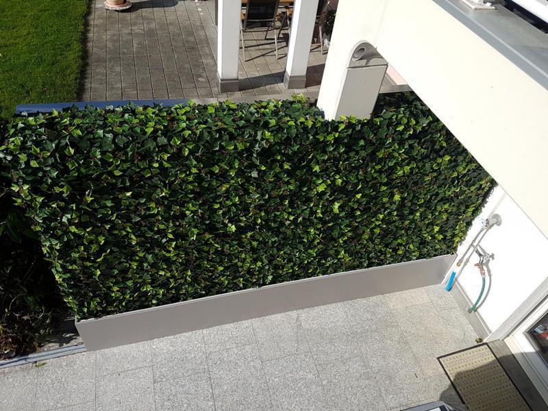Massgefertigte Efeu Kunsthecke im Garten als Sichtschutz.