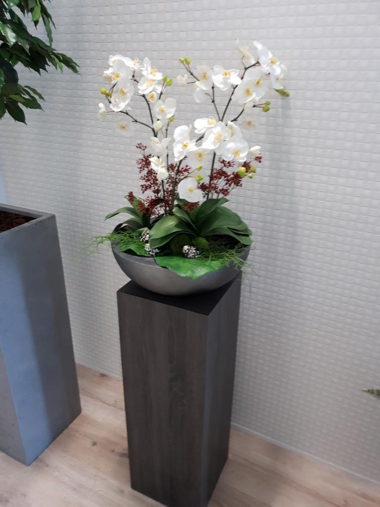 Ein Kunstblumen Arrangement mit Orchidee in einer Schale auf einer Pflanzsäule.
