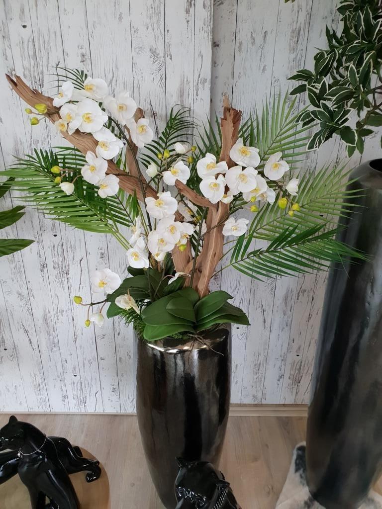 Begrünung Innen mit Kunstblumengesteck aus Orchideen und Treibholz in einer edlen Vase.