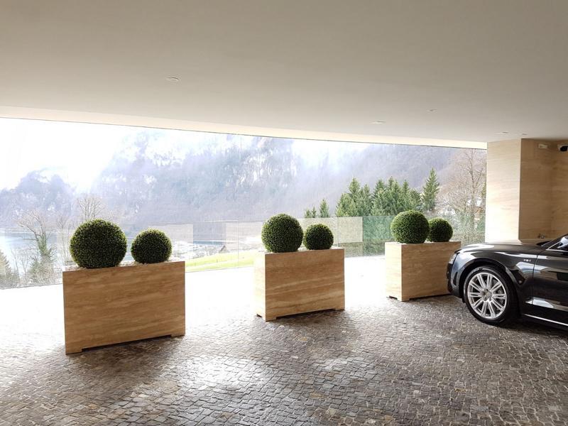 Terrassengestaltung mit exklusiven Pflanzgefässe und wetterfesten Buchskugeln, die künstlich sind.