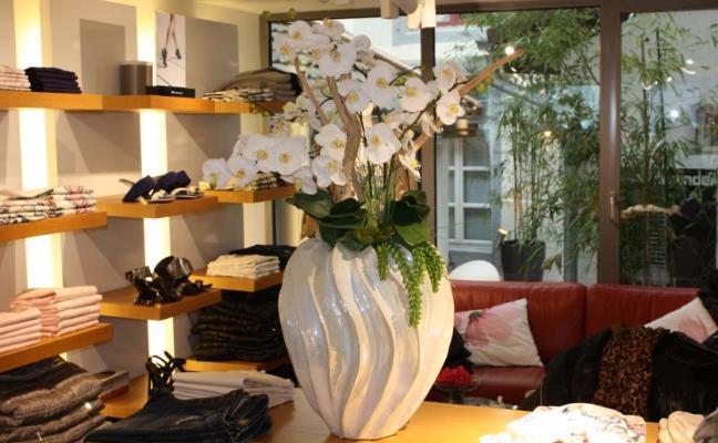BEgr¨nung einer Boutique mit einem künstlichen Orchideengesteck.