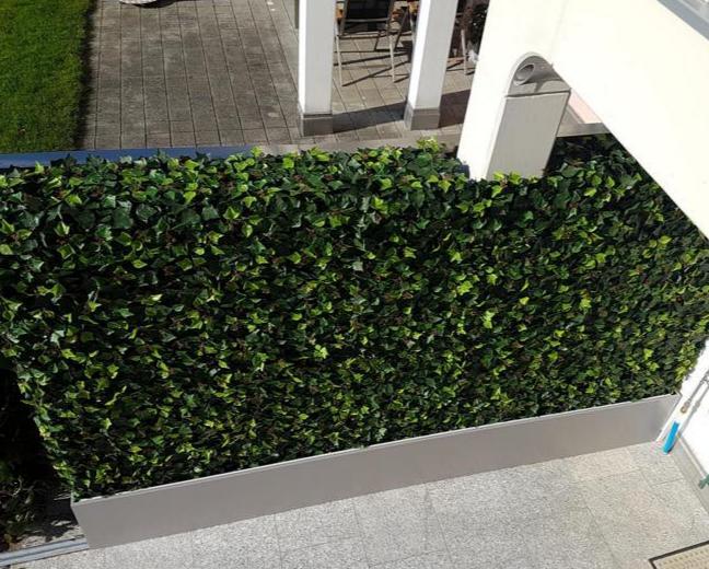 Gartengestaltung mit massgefertigter Hecke und Pflanzgefäss