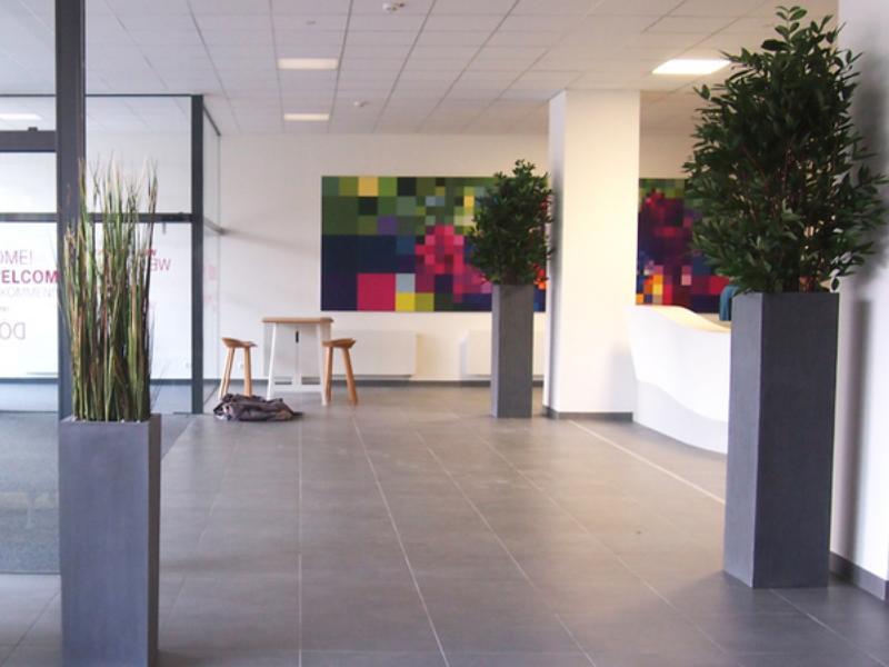 Raumgestaltung mit künstlichen Pflanzen in hohen Gefässen.