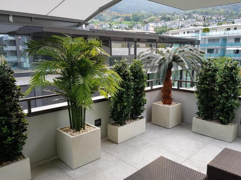Terrassengestaltung mit wetterfesten Kunstpflanzen und Hecken.